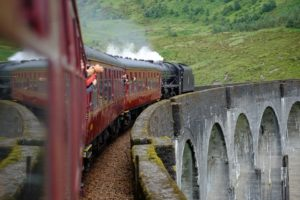 The Hogwarts Express train chugs along the track.