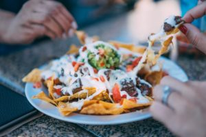 Two people sharing a plate of nachos.