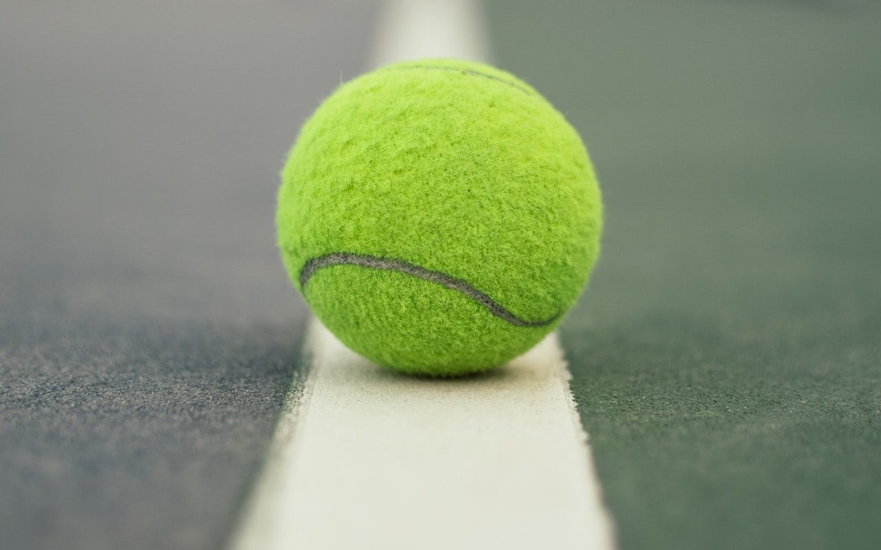 A tennis ball sits on a tennis court in Country Club Village.