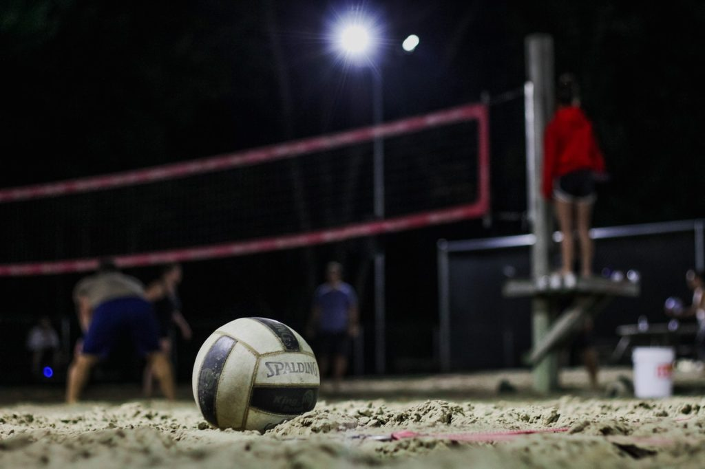 A volleyball sits on the sand volleyball courts in Country Club Village